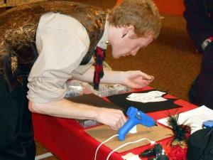 Gabriel hard at work making a trinket for a curious attendee.